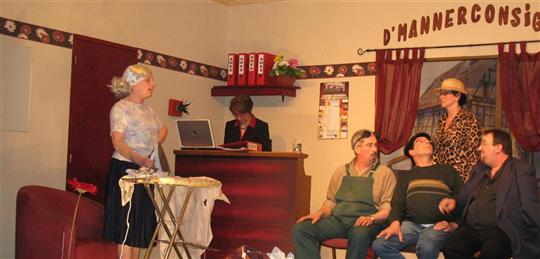 Des maris qui attendent à la consigne pendant que les épouses font leurs courses tranquillement.  Association Théâtre et loisirs d'Aspach-le-Haut